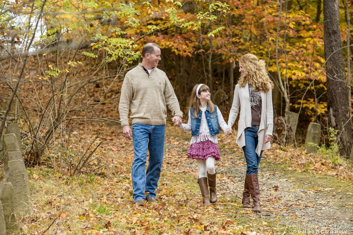 Family portrait session at the Cleveland Metroparks with mom, dad and daughter holding hands