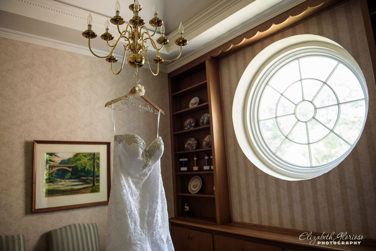 Picture of wedding dress hanging from chandelier