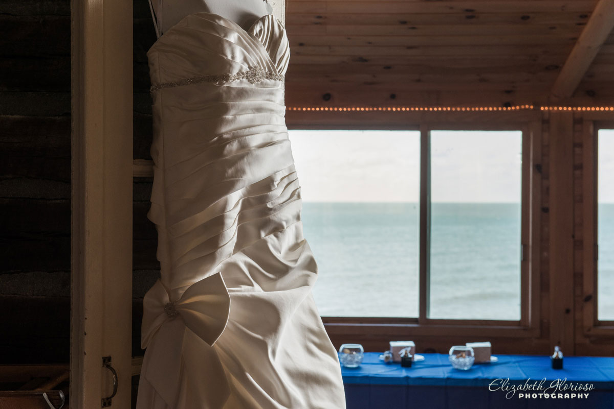 Photo of wedding dress hung up overlooking the water