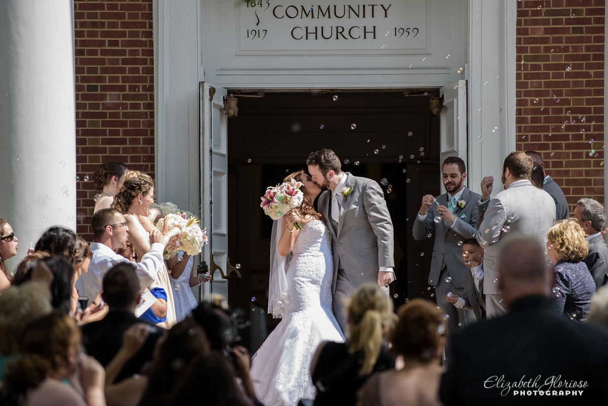Photo of bride and groom kissing outside of the Olmsted Community Church in Olmsted Falls, OH