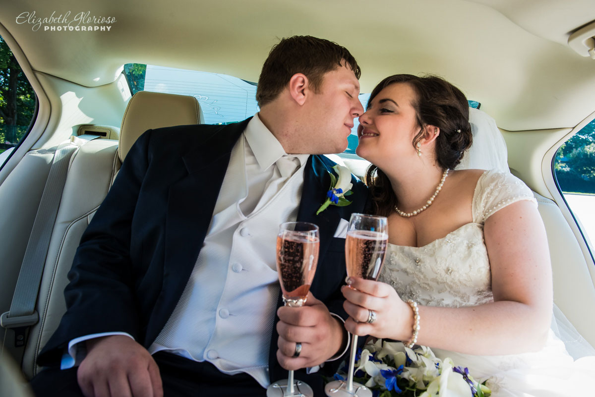 Photo of bride and groom holding champagne in a car near the Rockport Church in Cleveland, OH