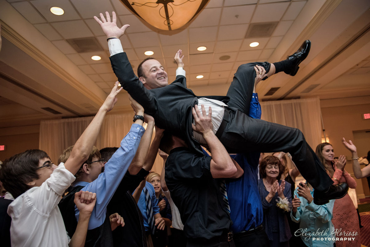 Picture of people dancing and holding up the groom at wedding reception at the Hilton Double Tree in Beachwood, OH