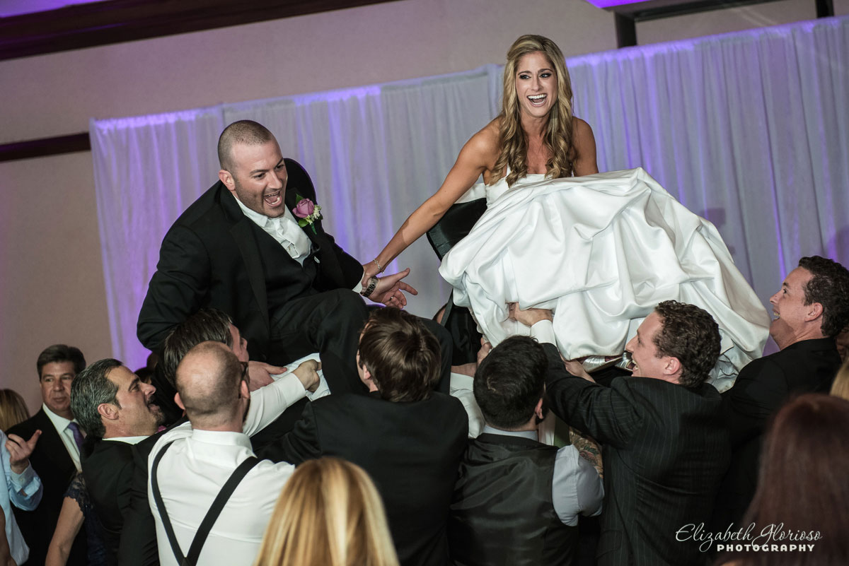 Picture of bride and groom being lifted on chairs at wedding reception held at the Cleveland Marriott East in Warrensville Heights, OH