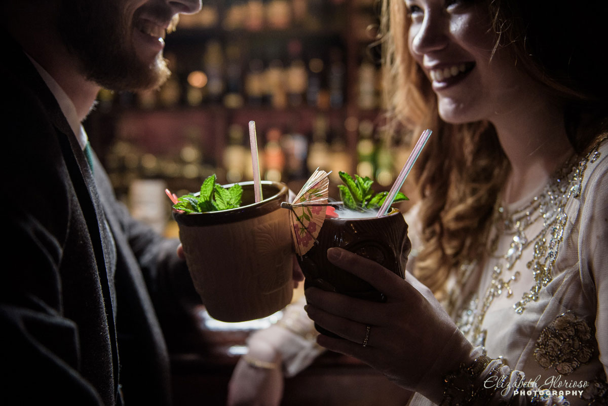 Photo of bride and groom with drinks at their wedding reception at Porco's Tiki Bar in Cleveland, OH