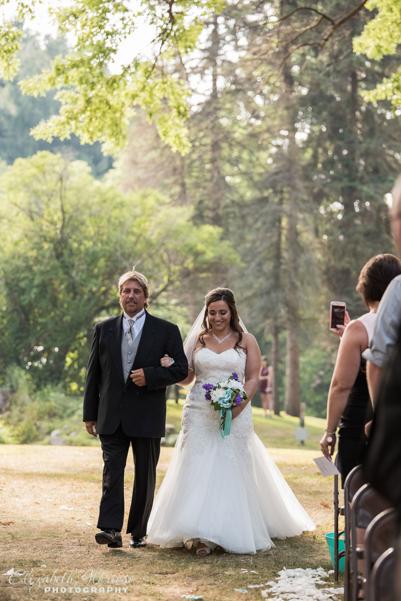 Photo of bride walking down the aisle with her father at The Tudor House in Akron, OH