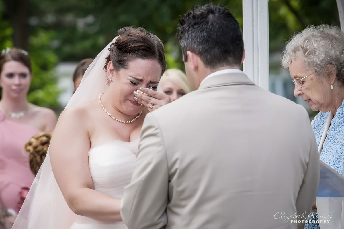 Photo of bride crying at her wedding ceremony at The Club House Vermilion-on-the-Lake