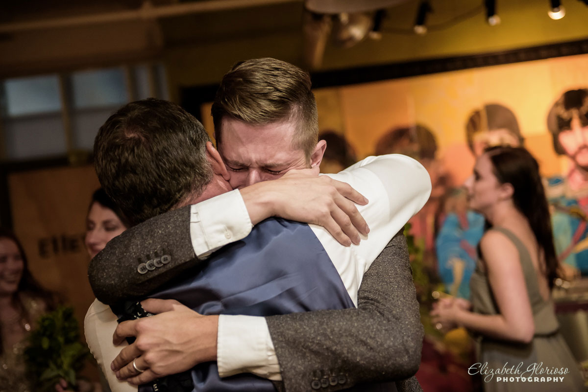 Photo of groom and groomsman hugging at wedding reception at SmArt Space West 78th Studios in Cleveland, OH