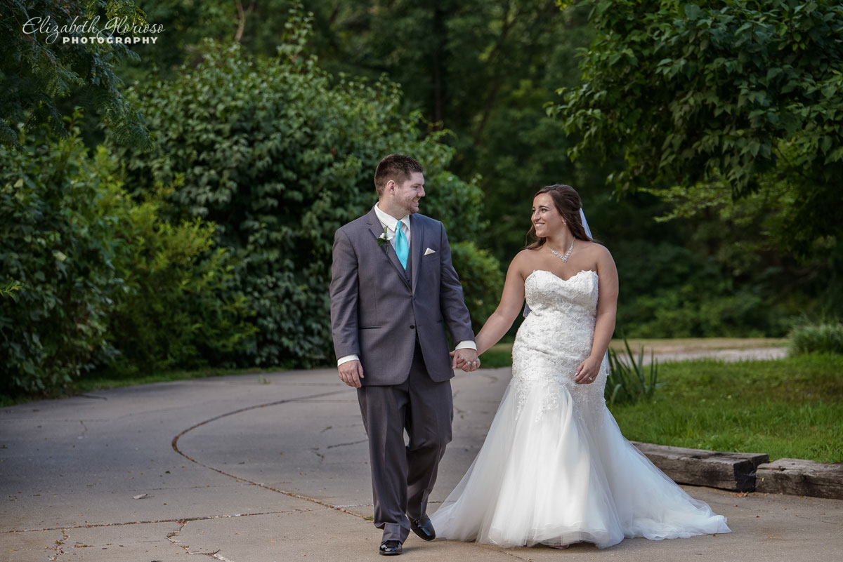 Photo of bride and groom hand-and-hand outside of the Tudor House in Akron, OH