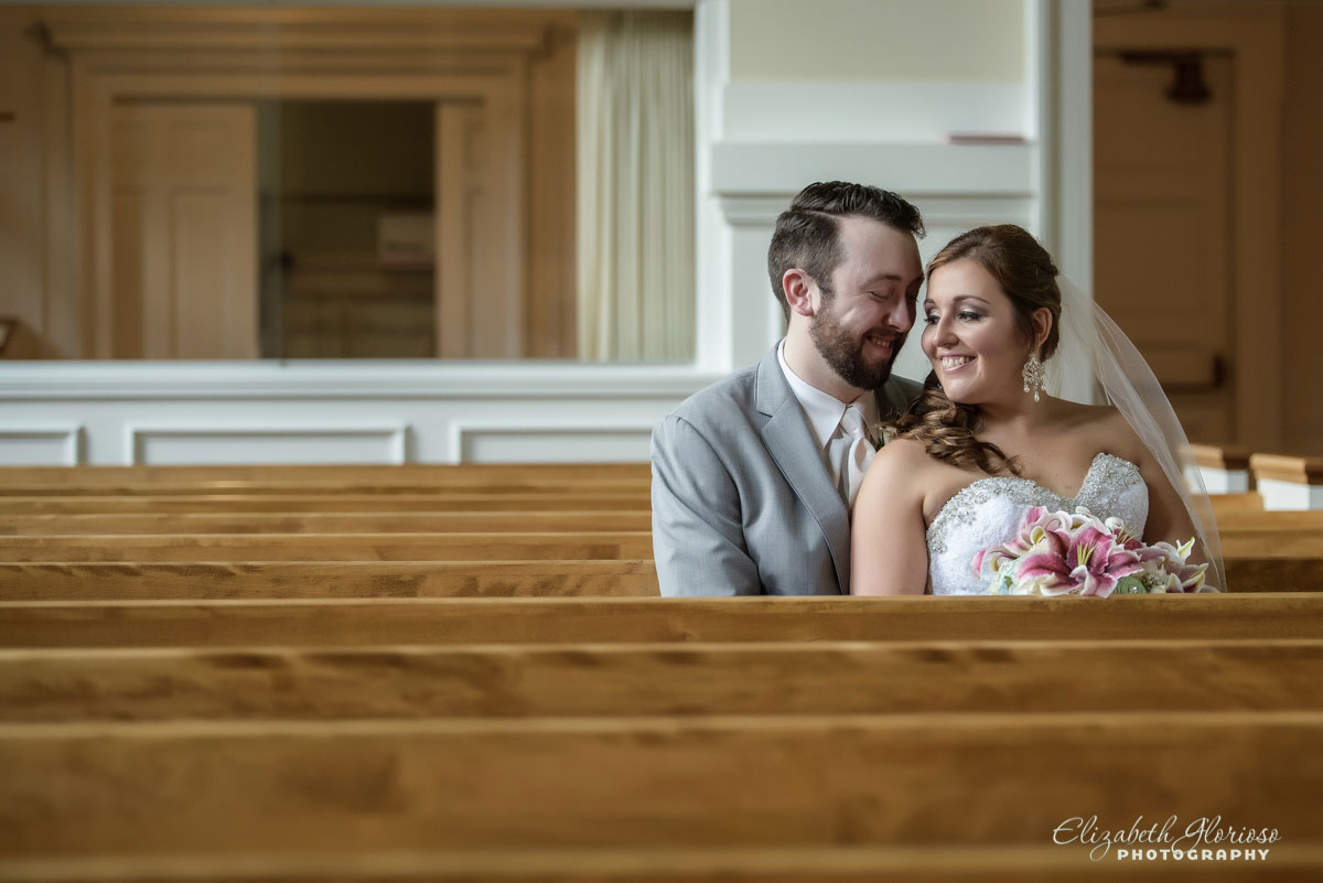 Photo of bride and groom sitting together in the pews at Olmsted Community Church in Olmsted Falls, OH