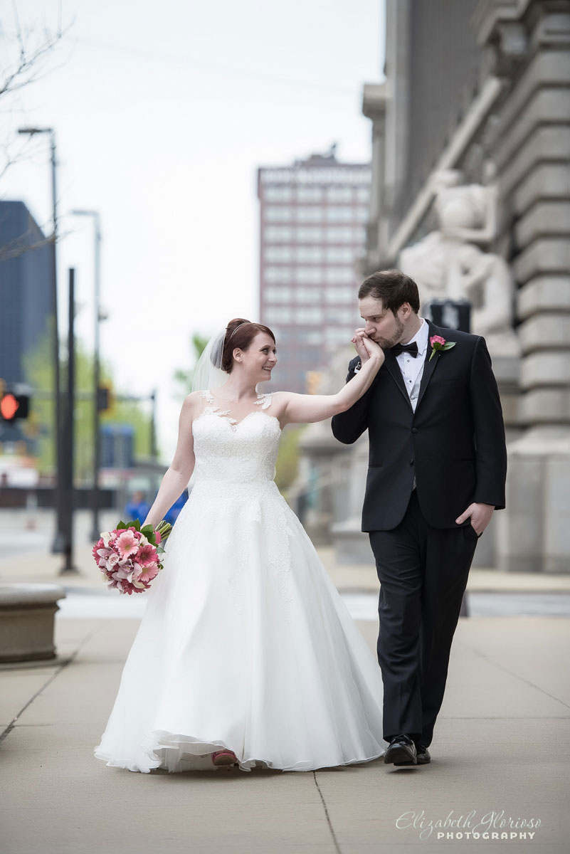 Photo of groom kissing bride's hand outside of the Cleveland Public Library
