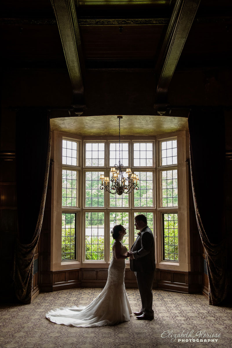Wedding portrait of bride and groom taken near a large window at Lake Forest Country Club in Hudson, Ohio